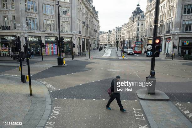 A man walks across a quiet Oxford Circus on March 20 2020 in London England Coronavirus has spread to at least 182 countries claiming over 10000...