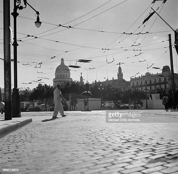 A man walks across a street underneath the electric cables for cable cars showing the Capital building in the distance in Havana Cuba