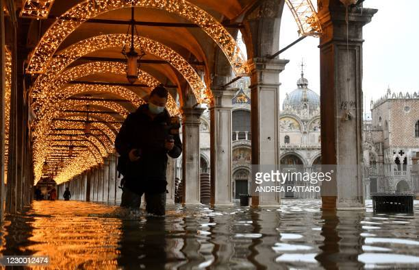 """Man walks across an arcade by a flooded St. Mark's Square on December 8, 2020 in Venice following a high tide """"Alta Acqua"""" event following heavy..."""