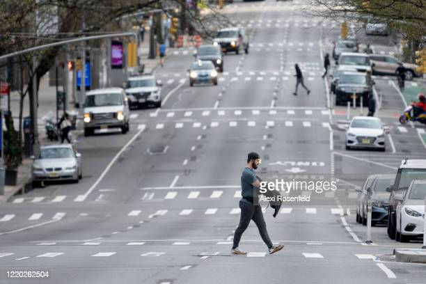 A man walks across an empty street amid the coronavirus pandemic on April 21 2020 in New York City United States COVID19 has spread to most countries...