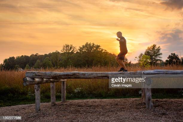 a man walks across balance beam outdoors silhouetted against sunset - balance beam stock pictures, royalty-free photos & images