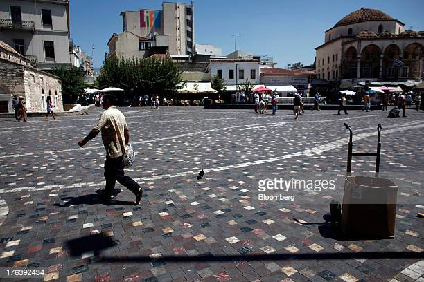 A man walks across Monastiraki square in Athens Greece on Friday Aug 9 2013 Greece's economy contracted for a 20th quarter extending an economic...