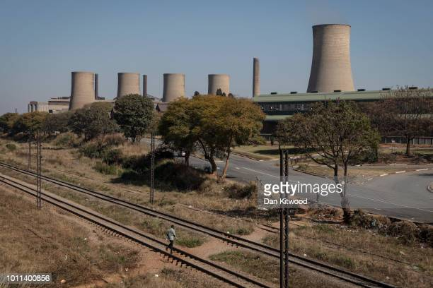 A man walks across rail tracks near Harare Power Station on August 05 2018 in Harare Zimbabwe Zimbabwe Electoral Commission officials have announced...