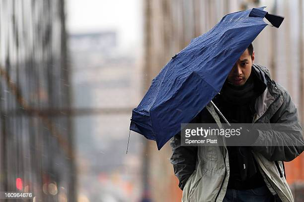 A man walks across the Brooklyn Bridge in the snow and sleet in the early hours of a major winter storm on February 8 2013 in New York City New York...