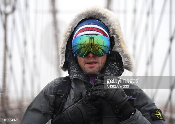A man walks across the Brooklyn Bridge on January 4 2018 in Brooklyn New York The US National Weather Service warned that a major winter storm would...