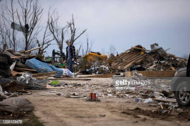 A man walks across the former spot of a home destroyed by a tornado at the top of a driveway on March 4 2020 in Cookeville Tennessee A tornado passed...