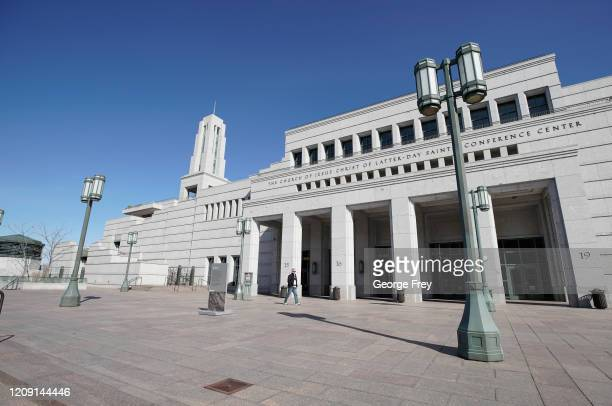 A man walks across the grounds of the Conference Center that sits empty for the 190th Annual General Conference of the Church of Jesus Christ of...