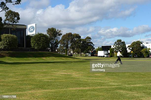Man walks across the lawn in front of Ford Motor Co.'s Australia head office building in Melbourne, Australia, on Thursday, May 23, 2013. Ford will...