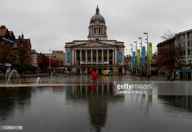 Man walks across the Old Market Square in Nottingham, central England as the city moves into Covid-19 Tier 3 restrictions on October 29, 2020.