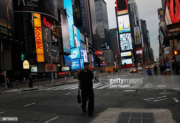 A man walks across Times Square at sunrise near where a crude car bomb had been parked at 45th Street and 7th Avenue May 2 2010 in New York New York...
