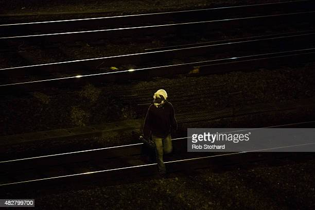 A man walks across train tracks near the Eurotunnel terminal in Coquelles on August 3 2015 in Calais France Hundreds of migrants are continuing to...