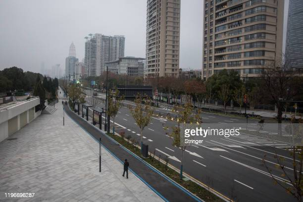 Man walks alone on an empty road on January 27, 2020 in Wuhan, China. As the death toll from the coronavirus reaches 80 in China with over 2700...