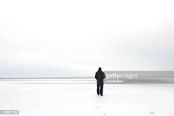 man walks alone on ice - parka coat stock photos and pictures