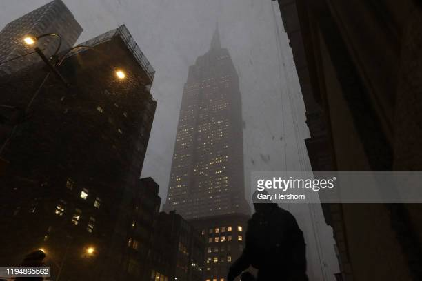 A man walks along 5th Avenue in front of the Empire State Building as a snow squall passes through Manhattan on December 18 in New York City