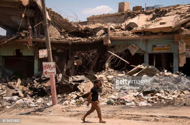 TOPSHOT A man walks along a damaged street in west Mosul on July 12 a few days after the government's announcement of the liberation of the embattled...