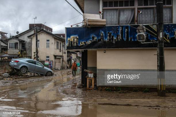 Man walks along a flood damaged street after the nearby Kuma River burst its banks, on July 5, 2020 in Hitoyoshi, Japan. Around 16 people are...