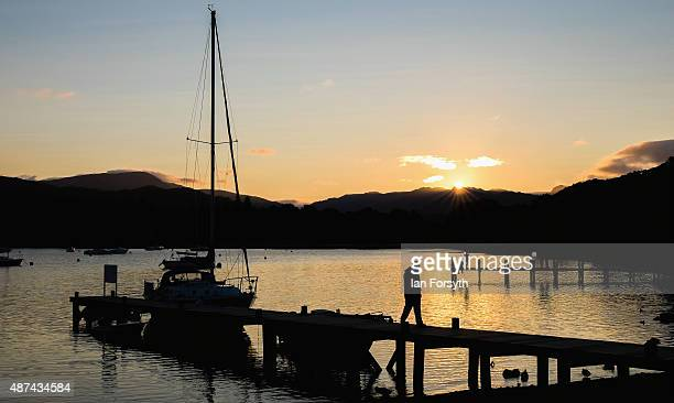 Man walks along a jetty at sunset after mooring his yacht at Waterhead on the northern end of Lake Windermere on September 06, 2015 in Windermere,...