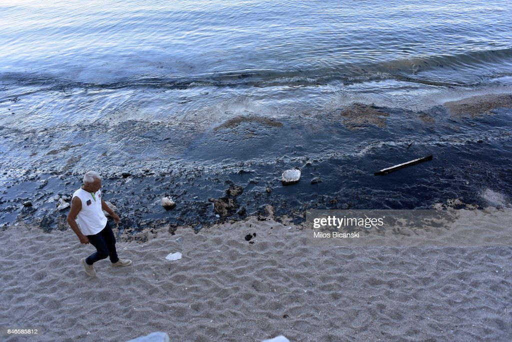 A man walks along a polluted beach on the coast of Salamis Island on September 13, 2017 in Salamis, Greece. The small tanker 'Agia Zoni II' sank on September 10, whilst anchored off the coast of Salamis, near Greece's main port of Piraeus. It was carrying a cargo of 2,200 tons of fuel oil and 370 tons of marine gas oil. Salamis Island has suffered heavy pollution as a result in what has been called a 'major environmental disaster' by officials.
