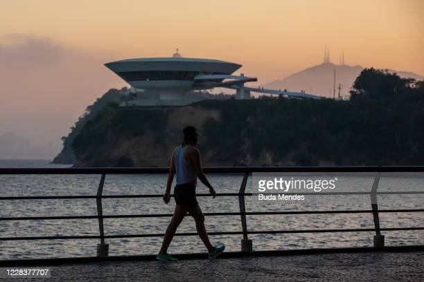 Man walks along a promenade with the Museum of Contemporary Art and the statue of Christ the Redeemer at the background on September 6, 2020 in...