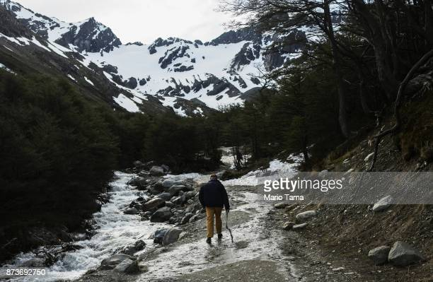 A man walks along a runoff stream below the retreating Martial Glacier on November 9 2017 in Ushuaia Argentina Ushuaia is situated along the southern...