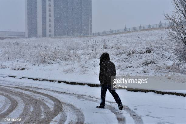 A man walks along a snowcovered road during a heavy snowfall in the winter season in Ankara Turkey on January 6 2019