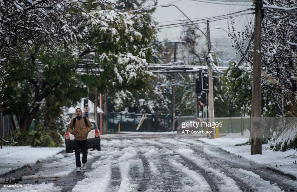 A man walks along a street covered with snow in Santiago on July 15, 2017. An unusual snowfall --the first of such intensity since 2007-- surprised the inhabitants of the Chilean capital, causing a few power cuts and minor traffic jams, in particular in the eastern areas of the capital, the closest to the Andes mountain range. / AFP PHOTO / Martin BERNETTI