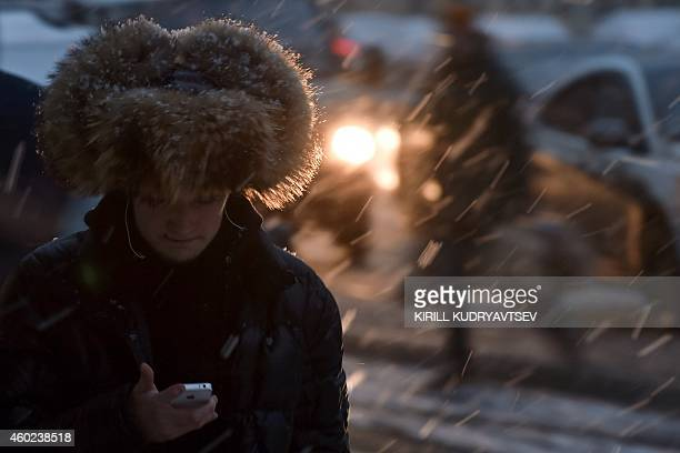 A man walks along a street in central Moscow during a snowfall on December 10 2014 AFP PHOTO / KIRILL KUDRYAVTSEV