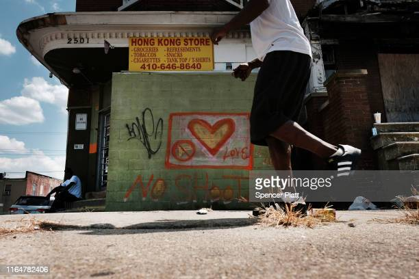Man walks along a street near where a person was recently murdered on July 28, 2019 in Baltimore, Maryland. President Donald Trump has recently drawn...