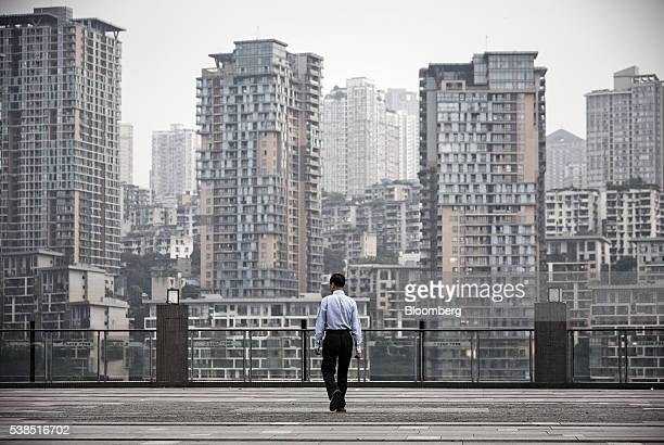 A man walks along a viewing platform in front of residential buildings in Chongqing China on Tuesday May 31 2016 The municipality of 30 million...