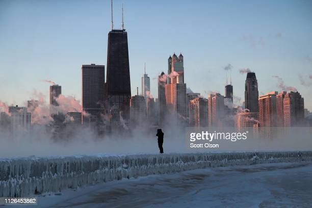 A man walks along an icecovered breakwall along Lake Michigan while temperatures were hovering around 20 degrees and wind chills nearing 50 degrees...