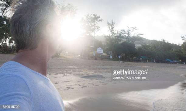 Man walks along beach edge at sunrise, near sea