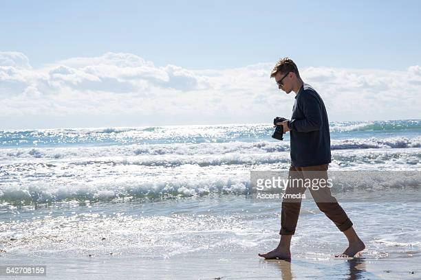 Man walks along beach, takes picture of surf