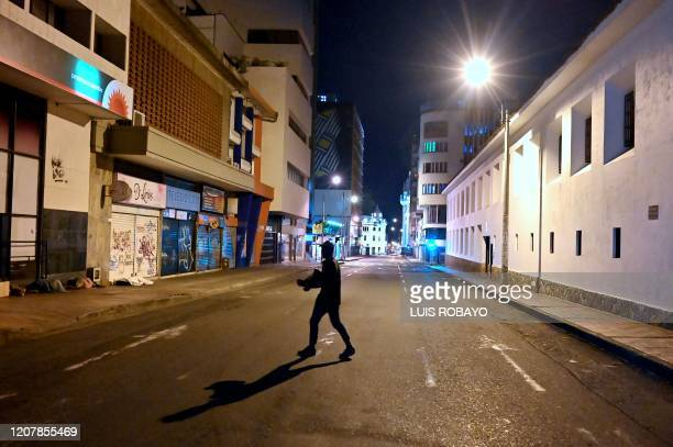 Man walks along of a empty street in Cali, Colombia, on March 20 as a consequence of measures taken against the spread of the new coronavirus,...