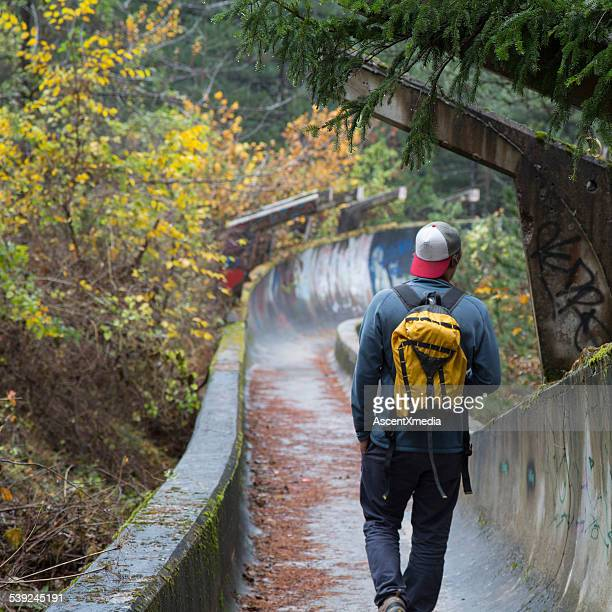 Man walks along overgrown track, in forest