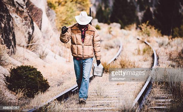Man walks along overgrown western railroad tracks carrying tools