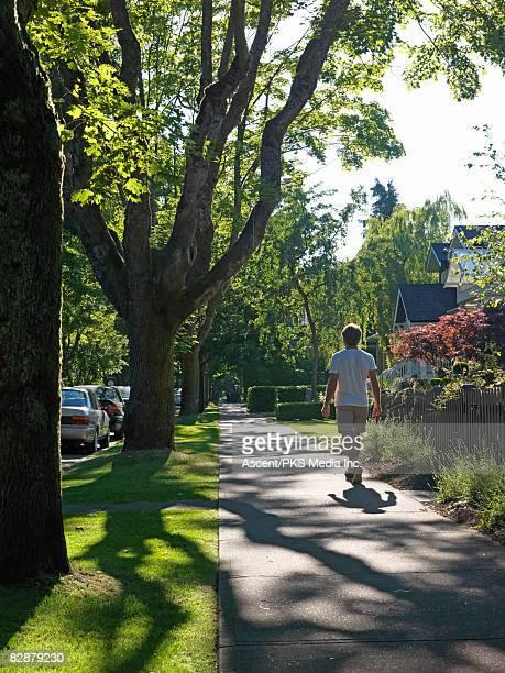 man walks along residential sidewalk - continente americano foto e immagini stock