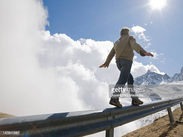 Man walks along road railing towards mountains