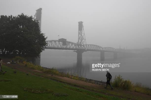 Man walks along the banks of the Williamette River in downtown Portland, Oregon where air quality due to smoke from wildfires was measured to be...