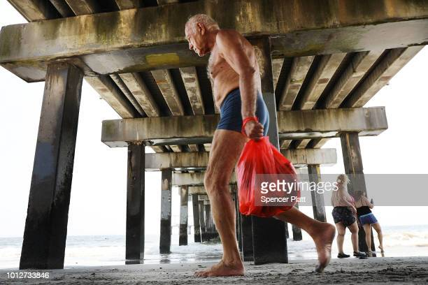 A man walks along the beach at Coney Island on a hot summer afternoon on August 7 2018 in the Brooklyn borough of New York City New York City is...