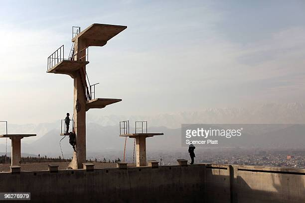 A man walks along the edge of an old Russian pool on a hill overlooking the city of Kabul on January 30 2010 in Kabul Afghanistan The then Soviet...