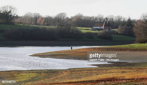 A man walks along the edge of Bewl Water reservoir near Lamberhurst in Kent as Southern Water applied for a drought permit amid flood alerts and...