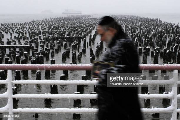 A man walks along the Hudson River during a snow storm on March 21 2018 in Jersey City New Jersey At least 12 to 15 inches are expected in parts of...