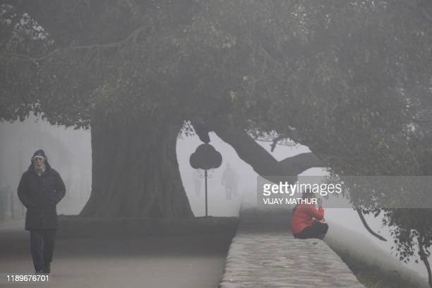 A man walks along the promenade of Sukhna Lake amid dense fog on a cold winter morning in Chandigarh on December 21 2019