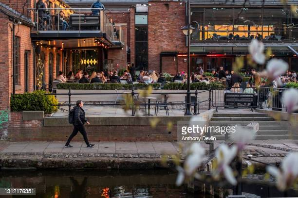 Man walks along the Rochdale canal as patrons sit in the beer garden at Dukes 92 bar on April 12, 2021 in Manchester, England. England has taken a...