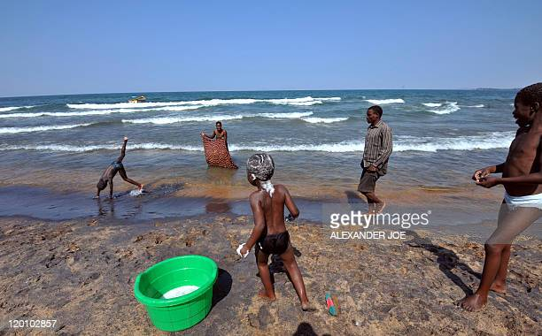 A man walks along the Saga beach as children wash themselves at Lake Malawi on July 17 2011 Lake Malawi remains unspoilt and one of Malawi's' biggest...
