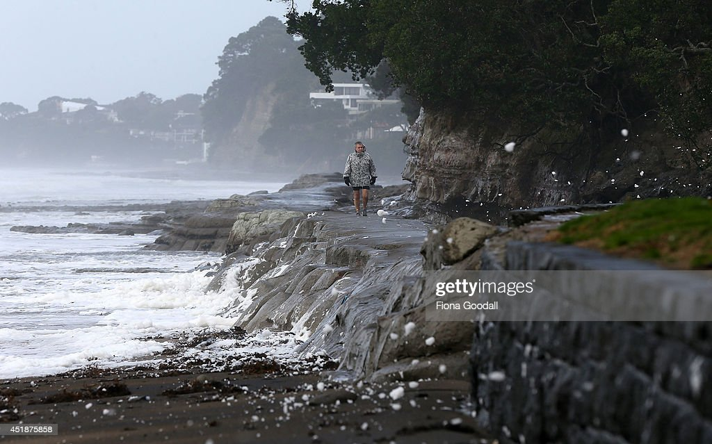A man walks along the shoreline as sea foam blows up the beach from gale force winds on July 9, 2014 in Auckland, New Zealand. A severe weather warning remains in place as wild weather hits Auckland, causing mass power outages, property damage, high winds and heavy rain.