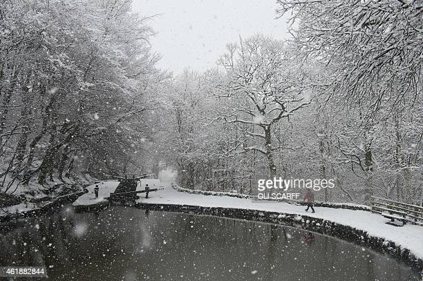A man walks along the snow covered towpath of the Huddersfield Narrow Canal in Marsden northern England on January 21 during heavy snowfall A Met...