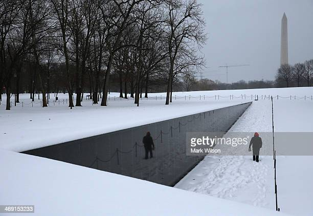 A man walks along the snow covered Vietnam Memorial on February 13 2014 in Washington DC The east coast was hit with a winter snowstorm with the...
