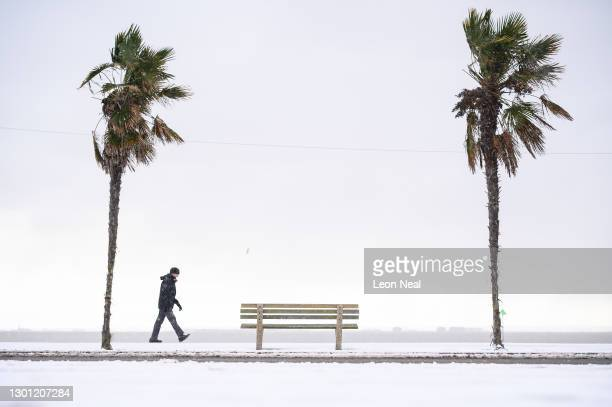 Man walks along the snow-covered promenade on February 09, 2021 in Southend, England. Heavy snow in Scotland and South East England over this weekend...