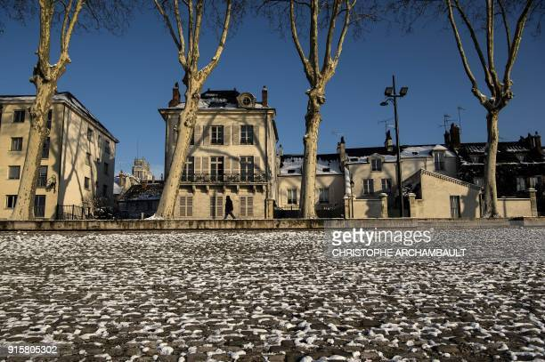 A man walks along the snowcovered quays of the Loire river in Orleans some 120 km south of Paris on February 8 2018 / AFP PHOTO / CHRISTOPHE...
